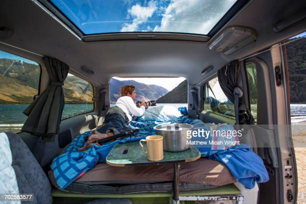A man sits in his campervan at a camp.