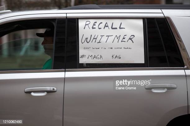 Man sits in his car while driving toward the Capitol along with many others to express their unhappiness with Governor Gretchen Whitmer's Stay Safe,...