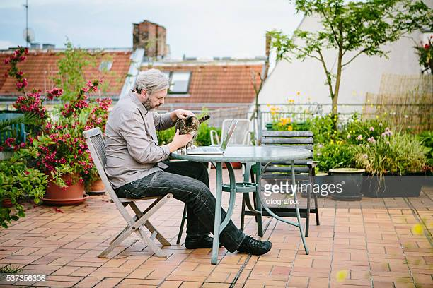 man sits in his roof garden and strokes his cat