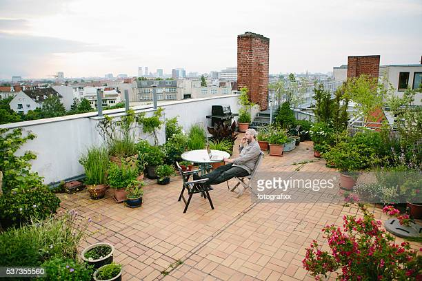 man sits in his roof garden, city skyline in background