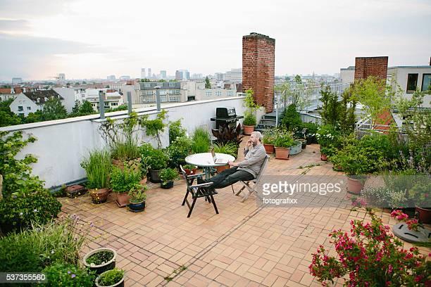 homem senta-se em seu jardim na cobertura, o horizonte da cidade no fundo - só um homem maduro - fotografias e filmes do acervo