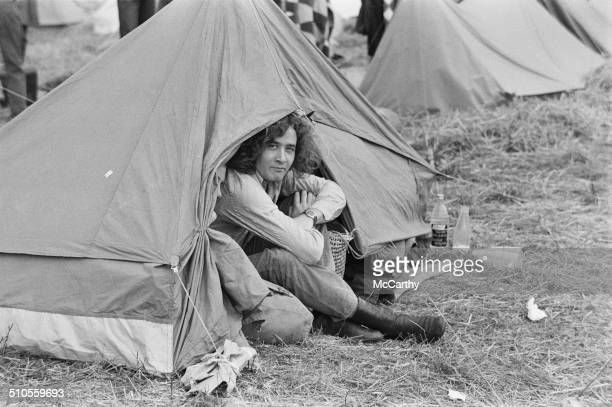 A man sits in his tent at the Isle of Wight Music Festival August 1969