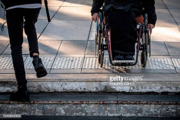 A man sits in his wheelchair on top of the stairs of a metro station in Paris on September 26 2018 during a demonstration called by the Paralysed...