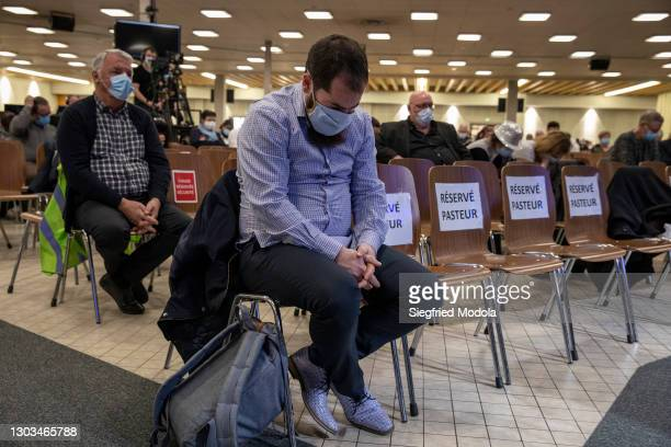 Man sits in prayer during Sunday mass at the evangelical Christian Open Door Church on February 21, 2021 in Mulhouse, eastern France. A multiday...