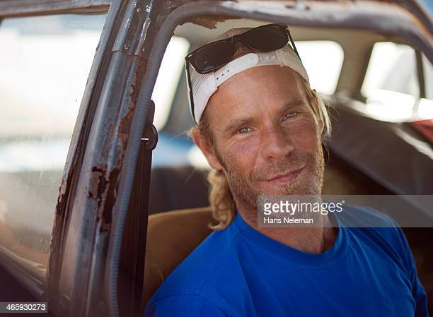 Man sits in rusted car