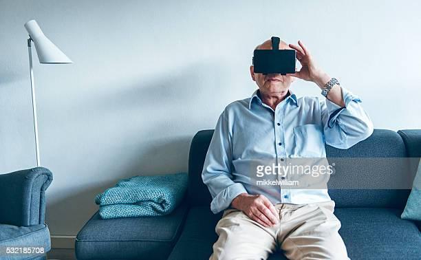 Mann sitzt im sofa vor dem Inhalt VR Gläser