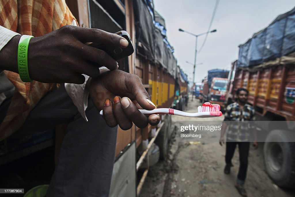 A man sits in the cabin of a truck looking at his phone while holding a toothbrush at the Sanjay Gandhi Transport Naga depot in New Delhi, India, on Thursday, Aug. 22, 2013. Indias rupee plunged 4.4 percent to a record this week in its worst performance since 1993 on signs the U.S. is getting closer to reducing stimulus that fueled demand for emerging-market assets. Photographer: Prashanth Vishwanathan/Bloomberg via Getty Images