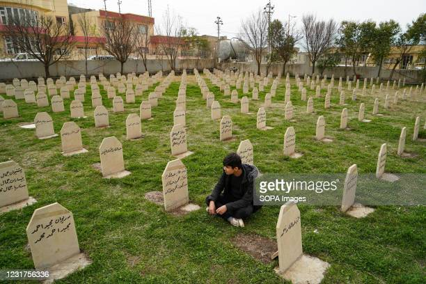 Man sits in the graveyard of the victims of the Halabja chemical attack. The 33rd anniversary of the chemical attack carried out by the Iraqi...