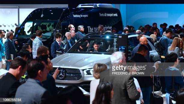 A man sits in the passenger side of a Mercedes Benz GLE Suv on display at AutoMobility LA the trade show ahead of the LA Auto Show November 28 at the...