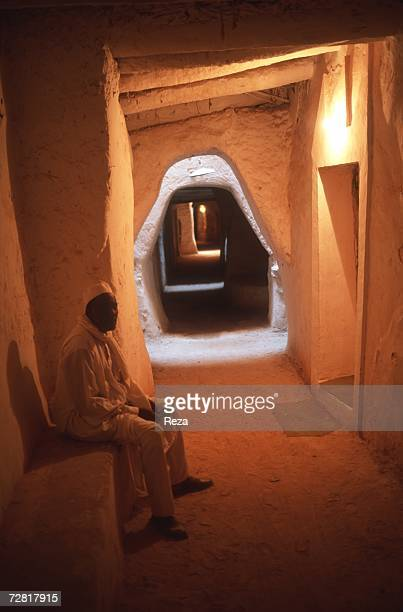 A man sits in the shadow of a small street April 2000 in Ghadames Libya
