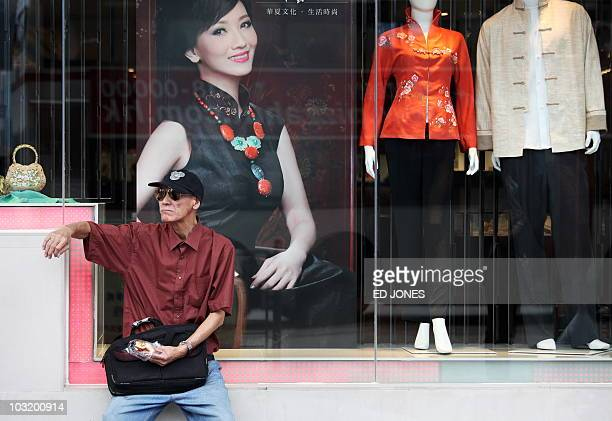 A man sits in the window of a clothing shop in the Kowloon area of Hong Kong on August 2 2010 Hong Kong's retail sales rose 153 percent in June from...