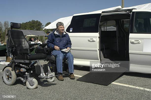 Man sits in wheelchair next to power wheelchair and van ramp display