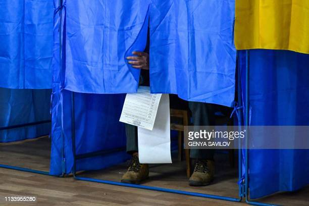 A man sits inside a voting booth at a polling station during Ukraine's presidential election in Kiev on March 31 2019