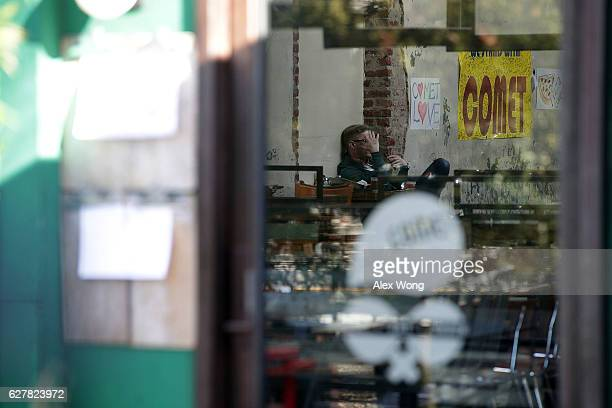 A man sits inside Comet Ping Pong pizzeria as he talks on his phone December 5 2016 in Washington DC A man was arrested Sunday after walking into the...