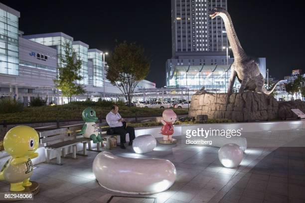 A man sits near a lifesize replica dinosaur in Dinosaur Plaza in front of Fukui station in Fukui Japan on Wednesday Oct 11 2017 Fukui Prefecture has...