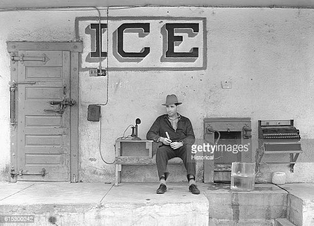 Man sits near a phone while trying to sell ice in winter. Harlington, Texas, February 1939.