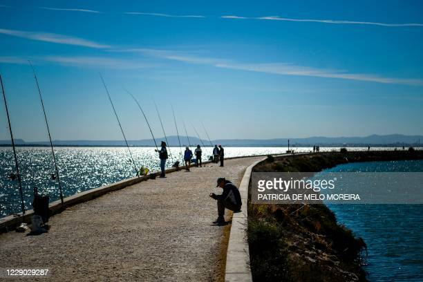 Man sits near silhouetted fishermen at Parque das Nacoes in Lisbon on October 12, 2020.