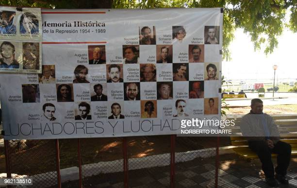 A man sits next to a banner depicting victims of Alfredo Stroessner's dictatorship during a ceremony in which the Paraguayan state offered an...