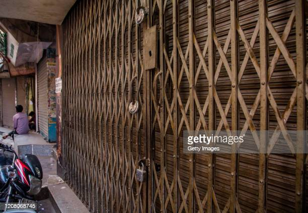 A man sits next to a closed shopping complex in a mostly deserted market during a lockdown order by Delhi's government as a preventive measure...