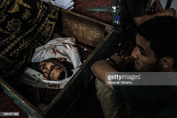 Man sits next to a coffin laid at Iman mosque which was turned into a makeshift morgue following the violent dispersal of Rabaa Adaweya square and...