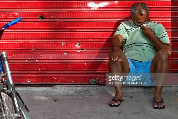 A man sits next to a metallic curtain with bullet holes at the Morro do Alemao shantytown on November 27 2010 in Rio de Janeiro Brazil Rio's slums...