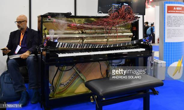 A man sits next to AMint an artificial intelligence piano at the 7th edition of the Maker Faire 2019 the greatest European event on innovation on...