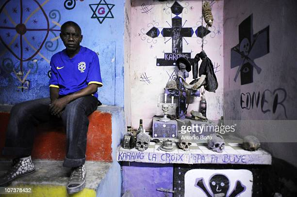 A man sits next to an alter with real human skulls and other Voodoo obejcts during the Haitian Day of the Dead November 1 2010 in Port au Prince...