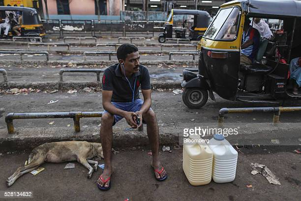 A man sits next to cans filled with water outside Mumbra railway station in Mumbai India on Sunday April 16 2016 Hundreds of millions of people in...