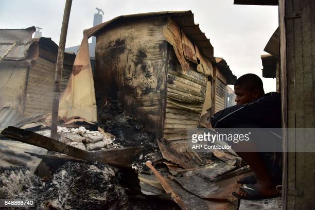 A man sits next to debris in the market after a fire devastated the building during the night on September 18 2017 in Abobo neighborhood of Abidjan /...