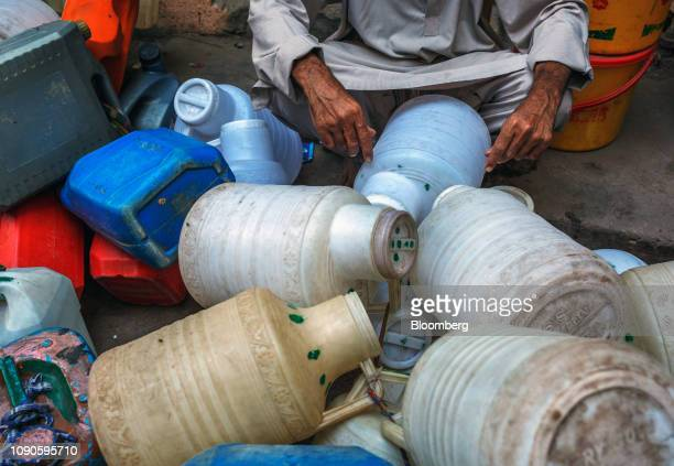 A man sits next to empty bottles and containers as he waits to collect water in Karachi Pakistan on Sunday Dec 23 2018 Women and children walk miles...