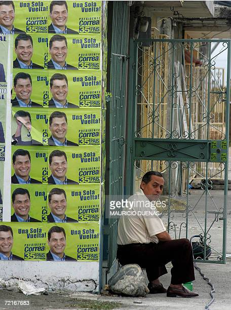 A man sits next to propaganda of presidential candidate Rafael Correa 14 October in the town of Recreo Guayas province Ecuador Leftist US critic...