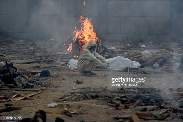 Man sits next to the body of a victim who died of the Covid-19 coronavirus besides the burning pyre of another victim at a cremation ground in New...
