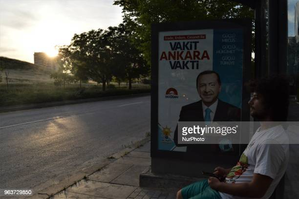A man sits next to the ruling Justice and Development Party's billboard picturing President Recep Tayyip Erdogan for the early presidential and...