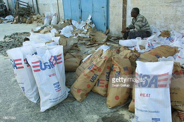 A man sits next to USdonated bags of wheat destined for Ethiopia February 21 2003 in Djibouti Town Djibouti The Food and Agricultural Organization...