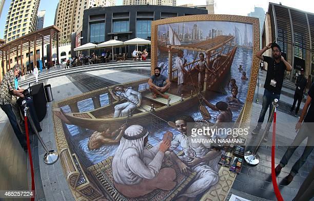 A man sits on a 3D artwork by US artist Kurt Wenner on March 4 2015 near the Jumeirah Beach Residence in Dubai during the Canvas Festival a...