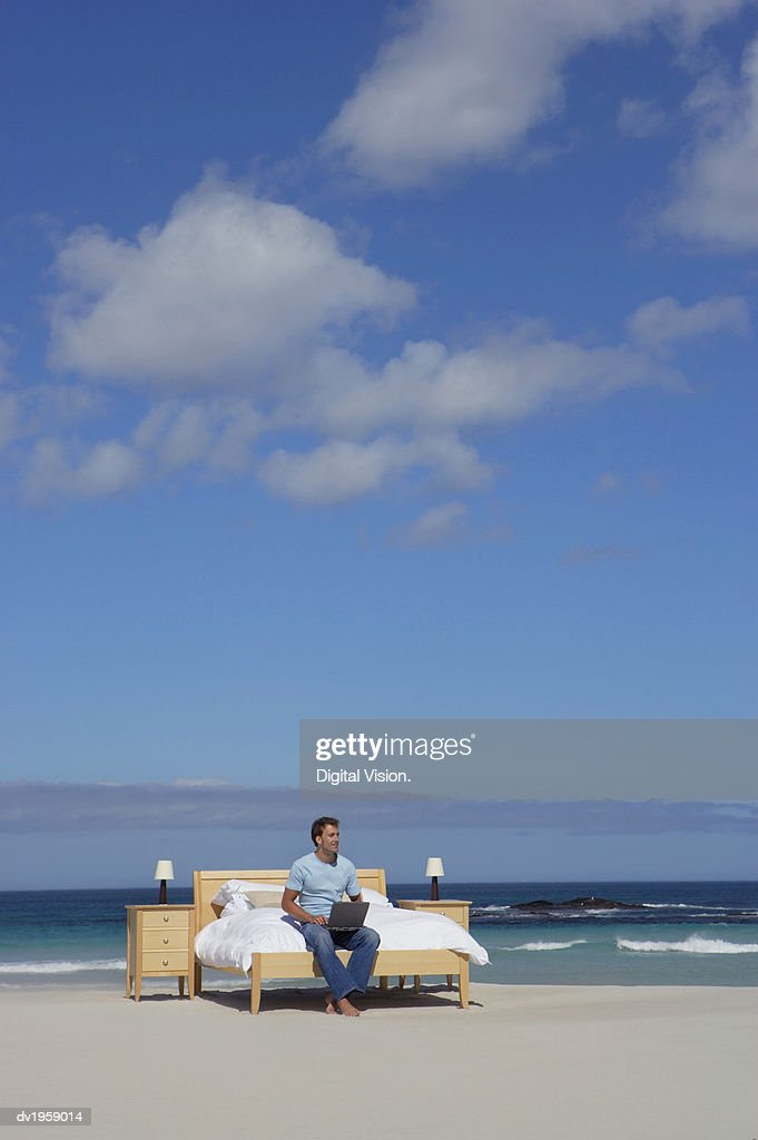 Man Sits on a Bed at the Edge of the Sea Using a Laptop : Stock Photo