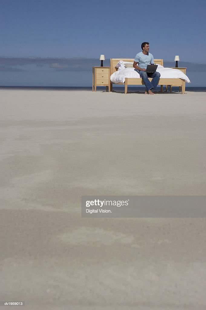 Man Sits on a Bed on a Beach Using a Laptop : Stock Photo