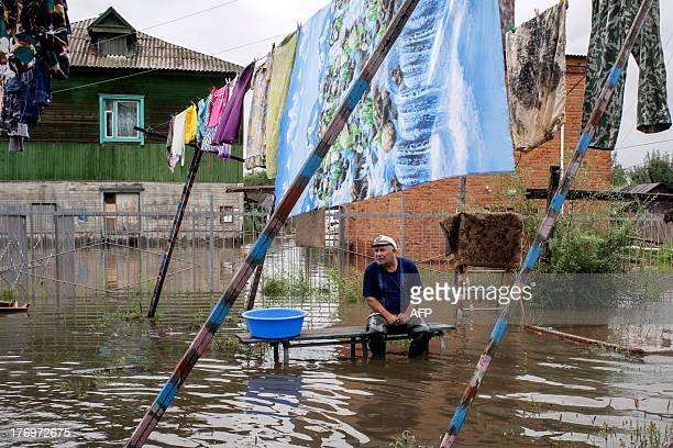 A man sits on a bench as clothes are hung to dry in a flooded street in the village of Bolshoi Ussuriysky island close to city of the Khabarovsk in...