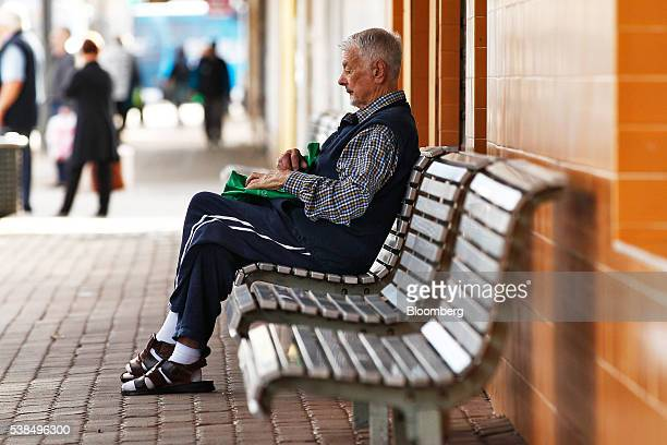 Man sits on a bench at a bus stop in the western suburb of Penrith in Sydney, Australia, on Monday, June 6, 2016. An economic divide is almost...