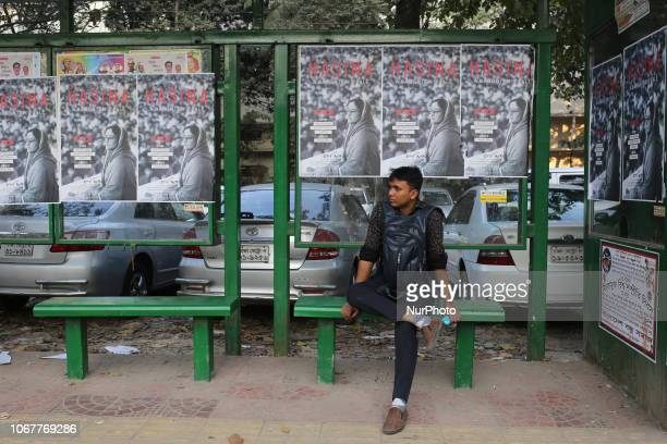 A man sits on a bench behind him posters of Hasina A Daughter's Tale a docudrama based on Bangladesh Prime Minister Sheikh Hasinas life in Dhaka on...