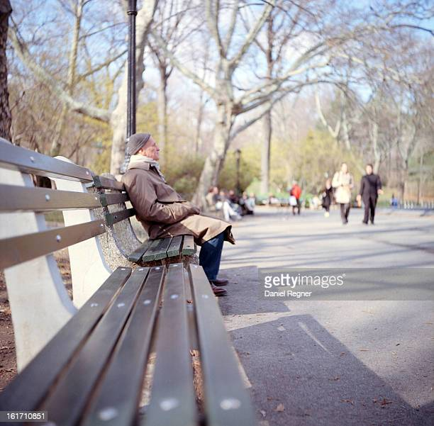 Man sits on a bench in Central Park, NYC. He is wearing a heavy coat, in the wintertime.