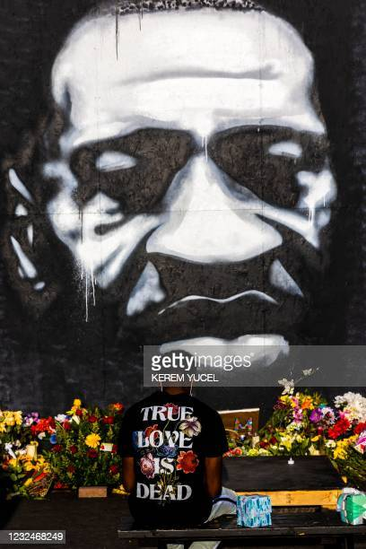 Man sits on a bench in front of a mural of George Floyd at George Floyd Square in Minneapolis, Minnesota, April 22, 2021.