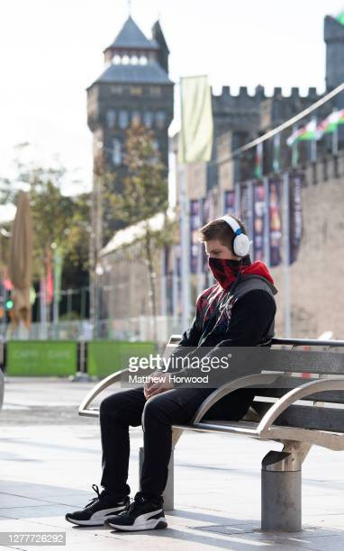Man sits on a bench in front of Cardiff Castle with his face covered on September 25, 2020 in Cardiff, Wales. A local lockdown for Cardiff comes into...