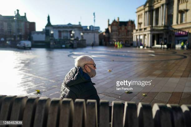 Man sits on a bench in Hull town centre on November 13, 2020 in Hull, England. Hull recorded 726.8 new cases per 100,000 people in the week to...