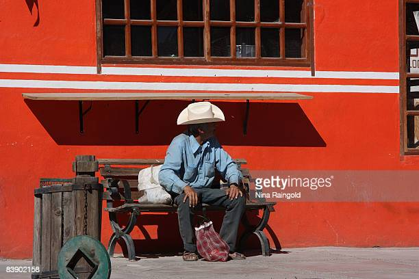 Man sits on a bench in the small farming and logging town of Creel on November 25, 2008 in Mexico. Creel is one of the main tourist attractions along...