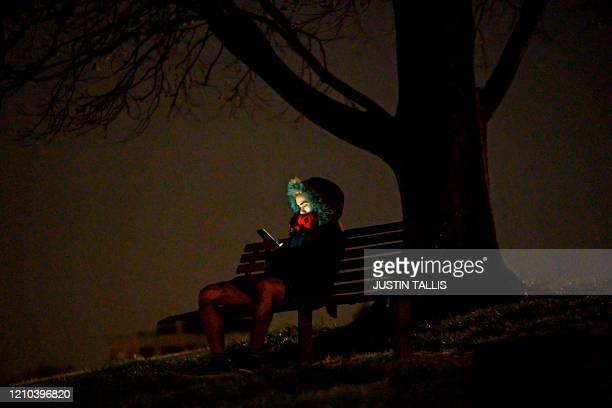 TOPSHOT A man sits on a bench looking at his mobile phone at night on Primrose Hill in London on April 18 during the novel coronavirus COVID19...