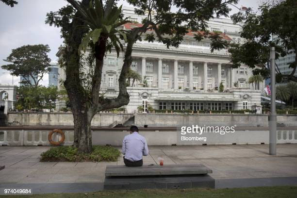 A man sits on a bench near the Fullerton Hotel in Singapore on Wednesday June 13 2018 Tourism as well as the consumer sector will likely see a lift...