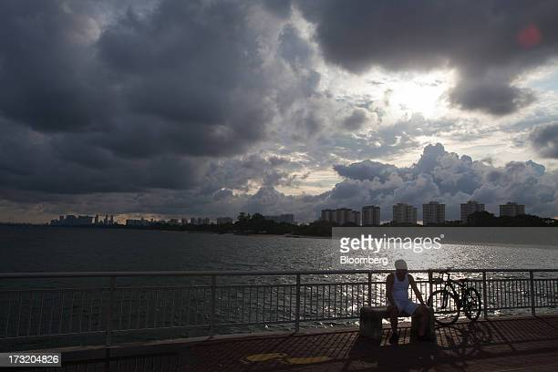 A man sits on a bench on Bedok Jetty as clouds hang over buildings in Singapore on Tuesday July 9 2013 Singapore will release secondquarter gross...