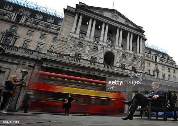 A man sits on a bench outside the Bank of England in London on October 25 2012 Britain powered out of its longest doubledip recession since the 1950s...