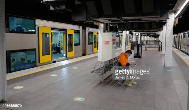 Man sits on a bench wearing a face mask whilst reading his mobile phone at Wynyard train station on August 15, 2020 in Sydney, Australia. New South...